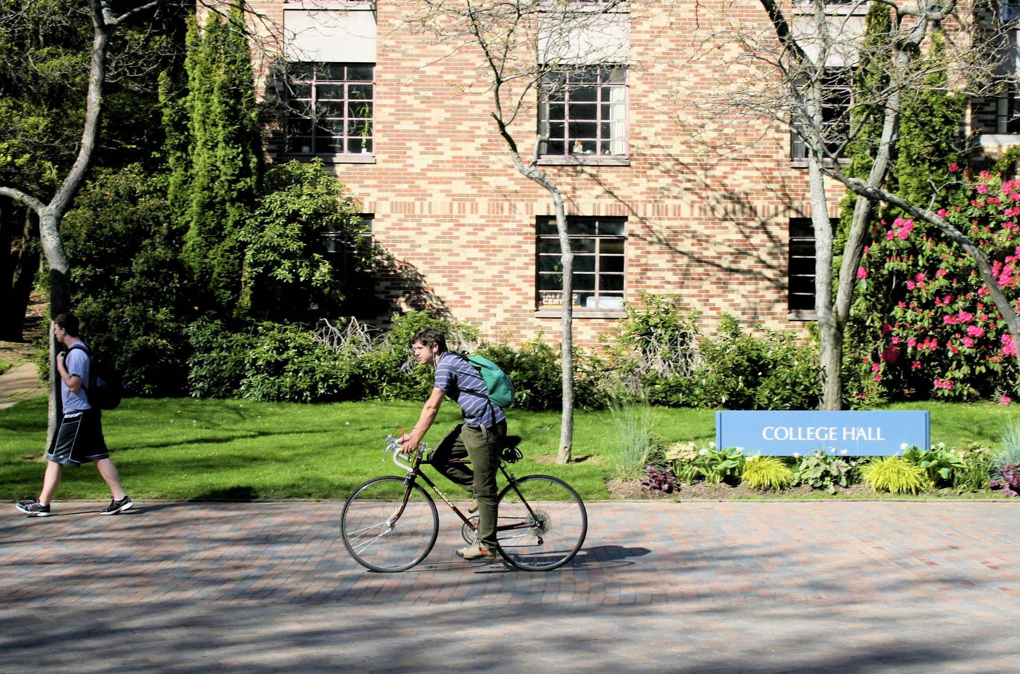 A student rides his bike past College Hall on a sunny day